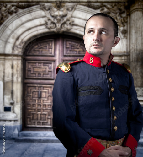 Antique soldier, man with military costume palace at background