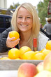 Junge Frau kauft Orangen auf Markt