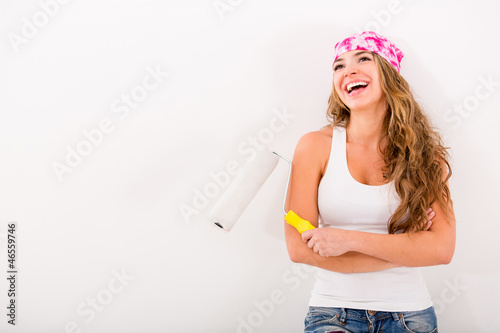Happy woman painting her house