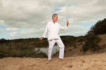 Senior spiritual man dressed in white. Exercising outdoors.