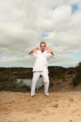 Senior spiritual man dressed in white.Exercising outdoors.