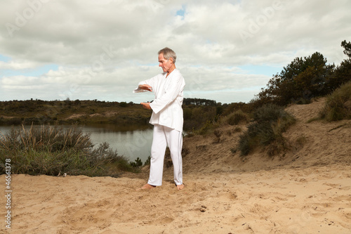 Senior spiritual man dressed in white.Exercising outdoors.
