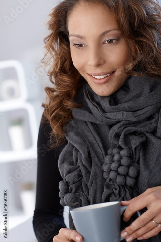 Smiling woman in scarf with tea mug