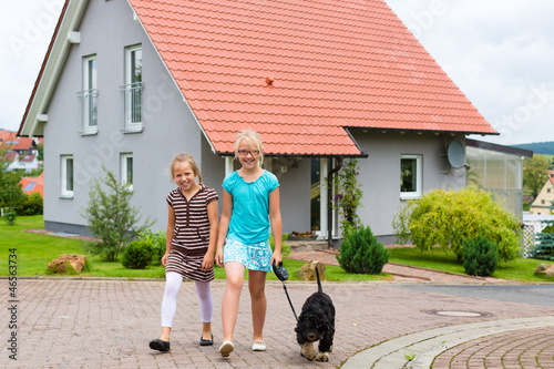 Two girl or children walking with dog