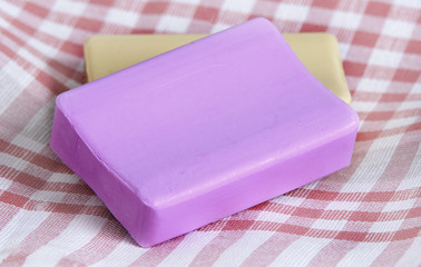 Two new pieces of soap, pink and yellow, on a checkered napkin