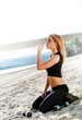 Woman drinking water on the beach after a workout