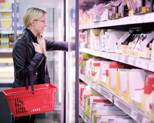 Junge Frau an der Kühltheke