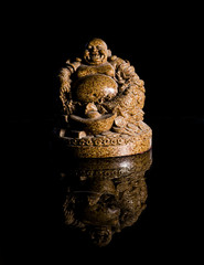 a brown lauphing buddha with reflection, black background