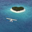 Wasserflugzeug fliegt auf Insel in Herzform Karibik zu