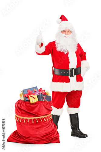 Santa Claus with a bag full of gifts giving a thumb up