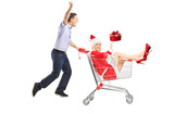 Happy guy pushing a female with gift in a shopping cart