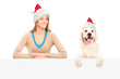 Smiling female and dog wearing santa claus hats and posing behin