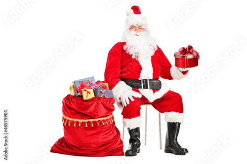 Santa Claus with a gift sitting next to a bag full of presents
