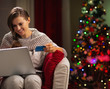Happy woman with laptop and credit card near Christmas tree