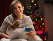 Smiling woman with tablet PC and credit card near Christmas tree