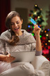 Happy woman in front of Christmas tree making online purchases