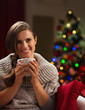 Happy young woman with cup of hot chocolate near Christmas tree