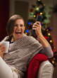 Excited young woman with cup of hot beverage looking TV