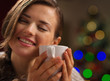 Young woman enjoying cup of beverage near Christmas tree