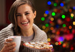 Happy woman holding cup of hot chocolate with marshmallows