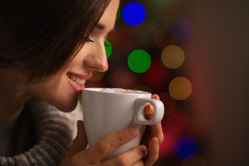 Happy young woman enjoying cup of  beverage near Christmas tree