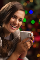 Happy young woman enjoying cup of chocolate near Christmas tree