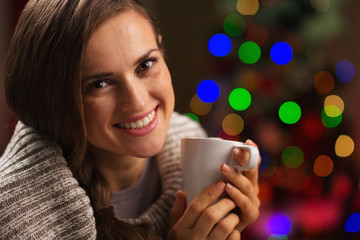 Happy woman enjoying cup of hot chocolate near Christmas tree