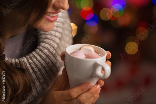 Closeup on hot chocolate with marshmallows in hand of woman