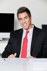 Happy Businessman Sitting At Desk