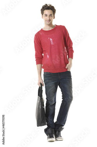 young attractive man carrying handbag  walking towards,