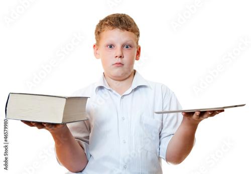 Мальчик держит в руках книгу и планшетный компьютер