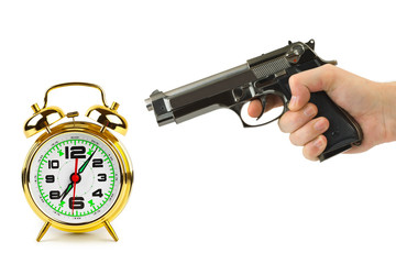 Hand with gun and alarm clock