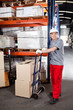 Warehouse Worker With Handtruck Loading Cardboard Boxes
