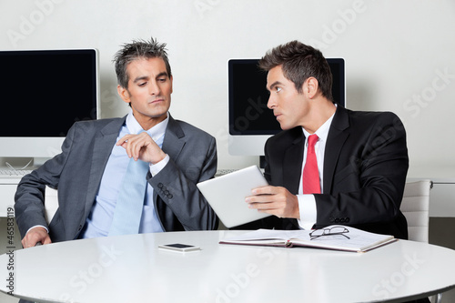 Businessmen Using Digital Tablet At Desk