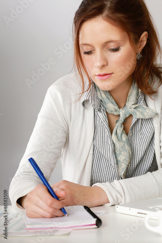 A woman at the desk writting on a paper
