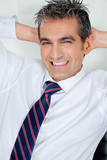 Mid Adult Businessman Relaxing With Hands Behind Head