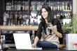 Woman on laptop in wine bar