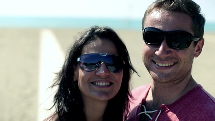 Portrait of smiling young couple on the beach, steadycam shot