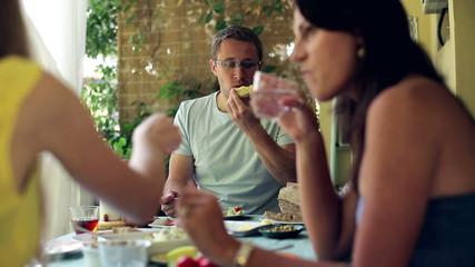 Three friends eating breakfast on the terrace, steadycam shot