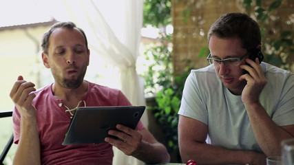 Two guys with tablet and smartphone sitting on the balcony