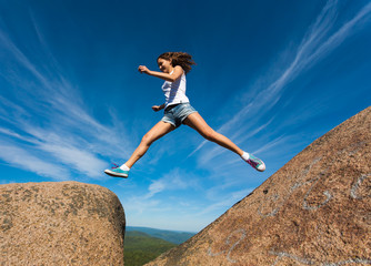 Young girl jumping on a rock