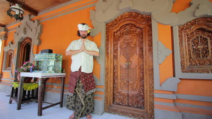caucasian man in balinese clothes saluting asian style
