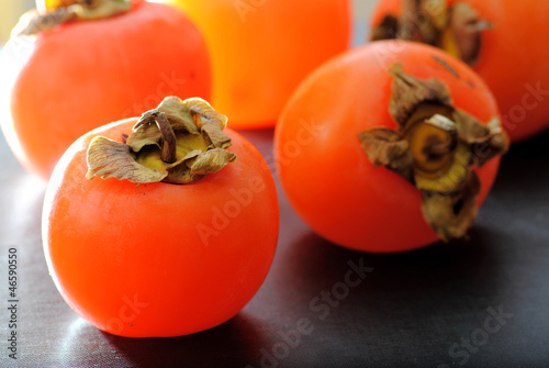 Close up fuyu persimmons fruits on black background