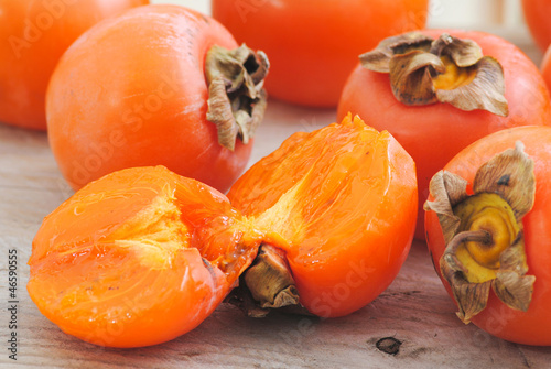 Close up fuyu persimmons fruits whole and cutted on white wood