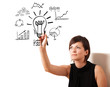 Young business woman drawing light bulb with various diagrams an