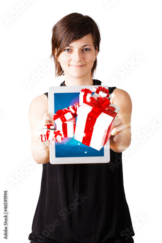 Young woman looking at modern tablet with present boxes