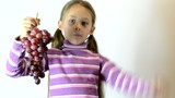 girl holding a bunch of grapes and shows thumb