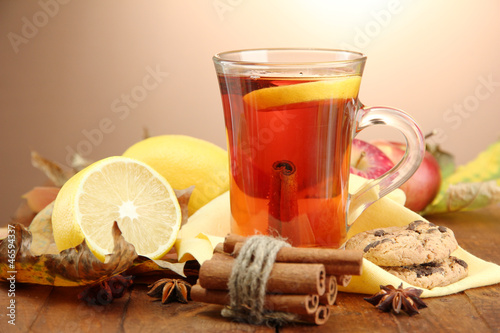 cup of hot tea and autumn leaves, on brown background