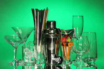 Cocktail shaker and glasses on color background
