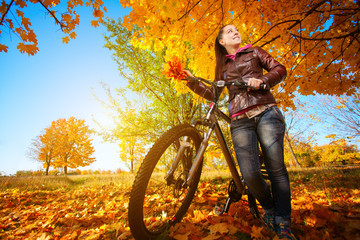 woman with bike on a autumn yellow leafs background